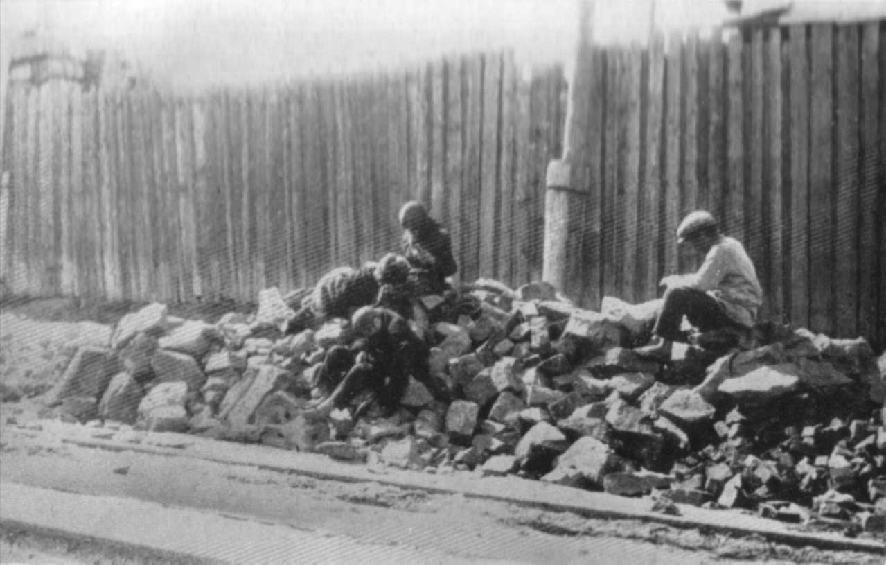 Безпризорники сидячи на купі каменю